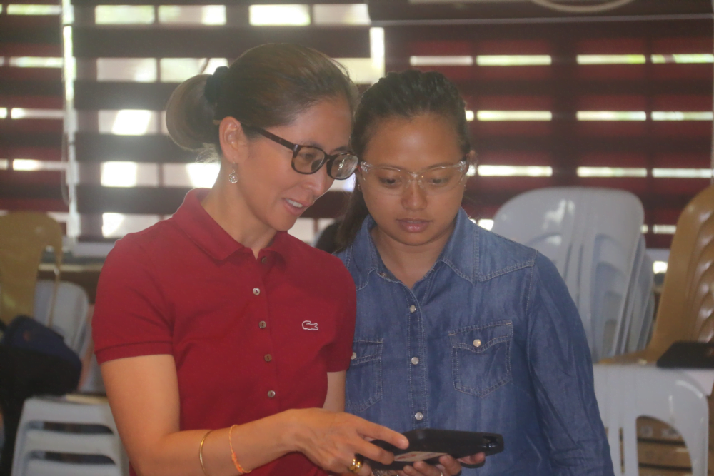 a drone instructor showing her trainee what's on the screen of the tablet she's holding