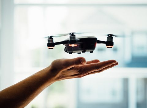 a small black drone landing in the extended open palm of a human