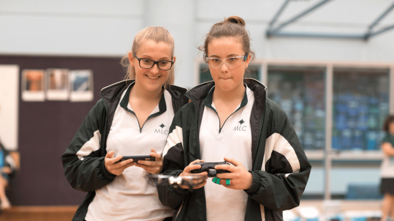 two female students from MLC engaged in their indoor drone lessons