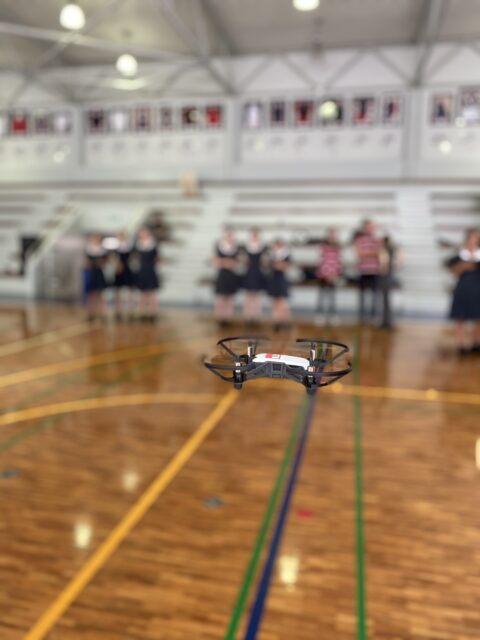 a black and white drone flying inside a school gymnasium