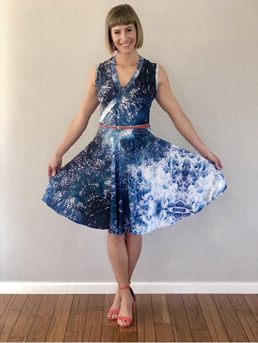 a woman wearing a dress with an image of the ocean captured by a drone