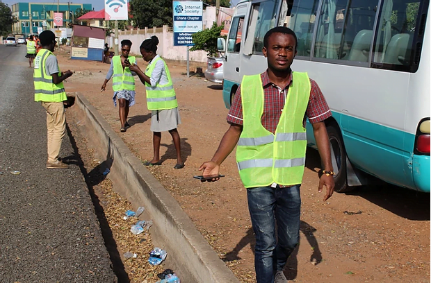 men and women in reflective vests by the roadside