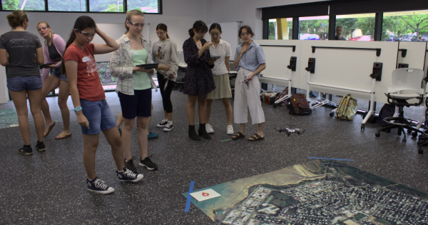 a group of female students looking at the image mat laid out flat on the floor as part of their drone lessons
